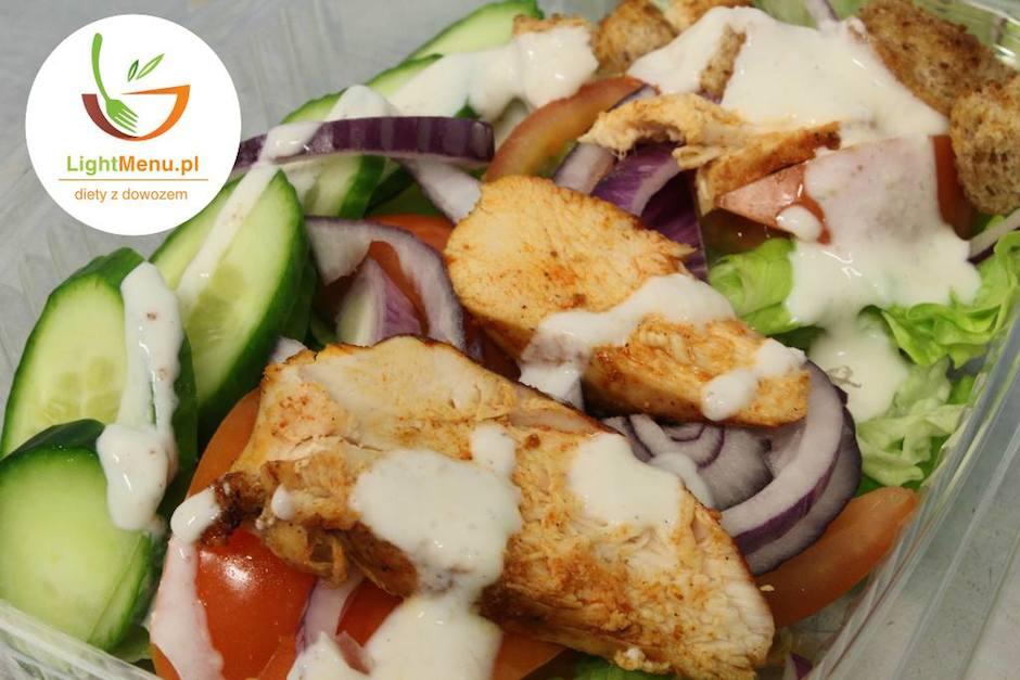 Wiosenna sałatka z pomidorem, ogórkiem, czerwoną cebulą i pieczonymi plastrami kurczaka w sosie jogurtowym.