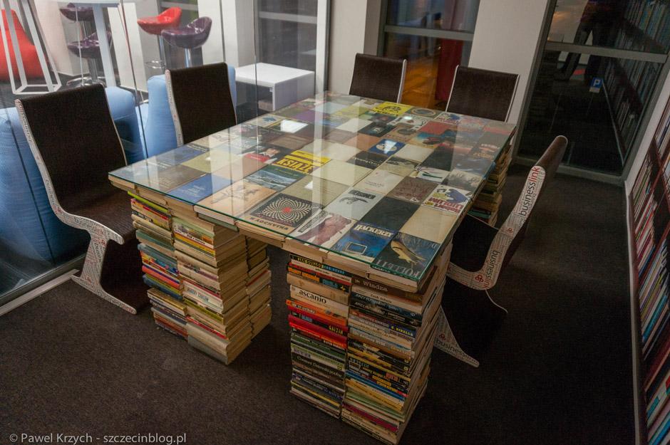 Pokój przeznaczony do spotkań z designerskim stołem z książek.