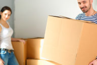 Happy young couple with boxes in new flat